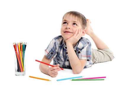 dreamy child boy with pencils on white background photo