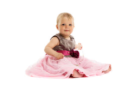 Adorable little baby girl in pink dress sitting on floor isolated on white background photo
