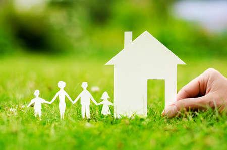Hand houden huis tegen groene veld Stockfoto