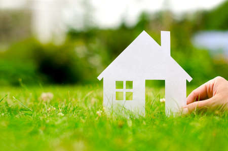 life insurance: Hand hold house against green field  Stock Photo