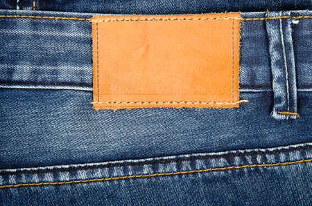 inner wear: Highly detailed closeup of blank grungy leather label on worn blue denim with orange seams, good for  Stock Photo