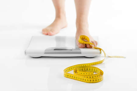 A picture of female feet standing on a bathroom scales and a tape measure over white background