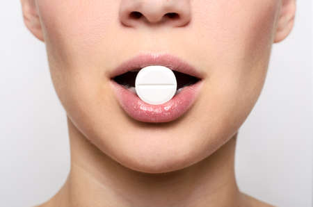 Beauty woman mouth with red lips and medicine pill on grey background Stock Photo