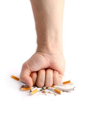 Mans fist crushing cigarettes isolated on white background
