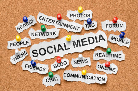 social media marketing: Social media from cutout newspaper headlines pinned to a cork bulletin board Stock Photo