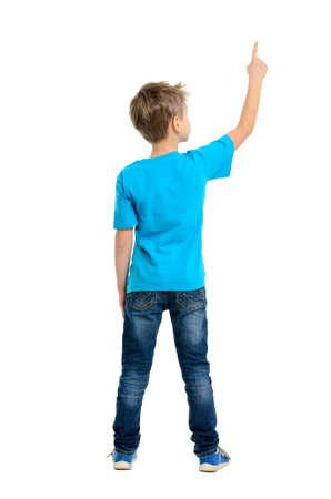 Vista trasera de un niño de la escuela sobre el fondo blanco que apunta hacia arriba Retrato de cuerpo completo Foto de archivo