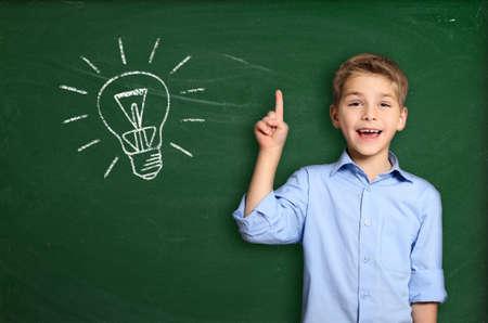 電球と黒板の近くに立って男子生徒 写真素材