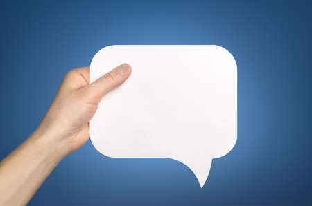 monologue: Hand holding an empty speech bubble on blue Stock Photo