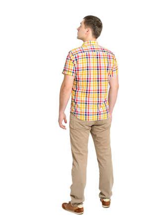 looking at view: Vista posteriore di giovane uomo in una camicia a quadri e jeans cercano piedi ragazzo Vista posteriore gente raccolta posteriore della persona Isolato su sfondo bianco Archivio Fotografico