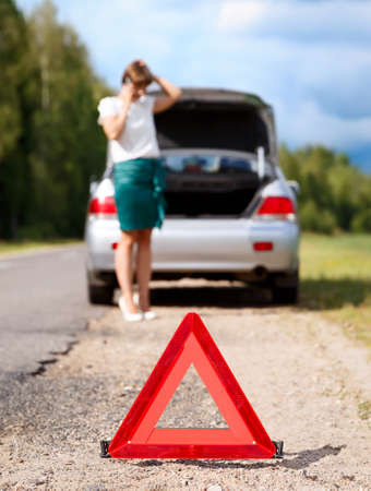 Close up on triangle warning sign with woman calling for assistance after breaking down with her car on background photo