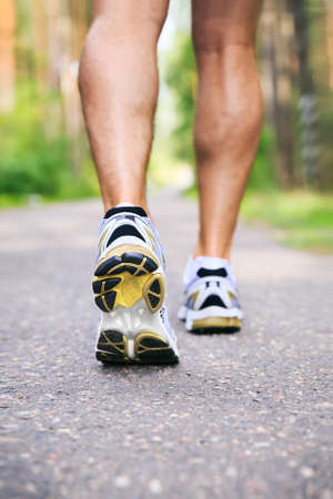 man legs: Jogging man. Running shoes and legs of male runner outside on road Stock Photo