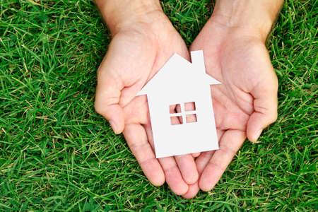 haus: Hand halten Haus gegen grünen Wiese, von oben gesehen.