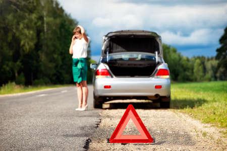 背景の彼女の車とともに分解後の支援を求める女性と三角形の警告のサインにクローズ アップ 写真素材