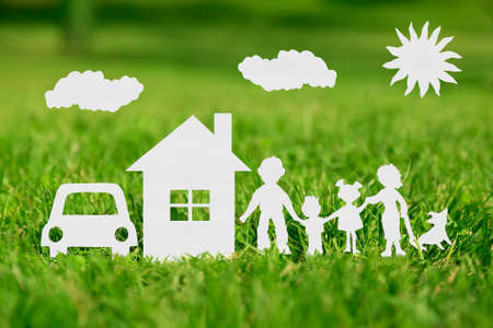 Paper cut of family with house and car on green grass Foto de archivo