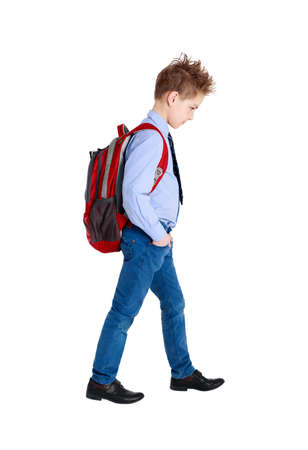 book bag: Full length portrait of a sad school boy walking, isolated on white background