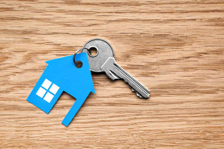 Silver key with blue house figure on wooden background
