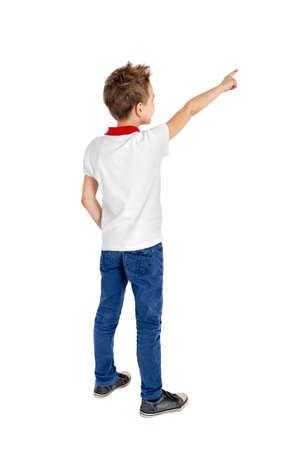 niño parado: Vista trasera de un niño de la escuela sobre fondo blanco apuntando hacia arriba. Retrato de cuerpo entero Foto de archivo