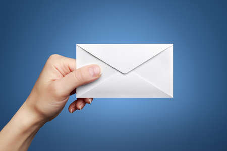 Womans hand holding closed envelope against blue background photo
