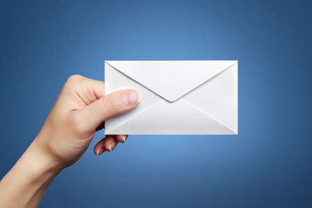 Womans hand holding closed envelope against blue background 版權商用圖片