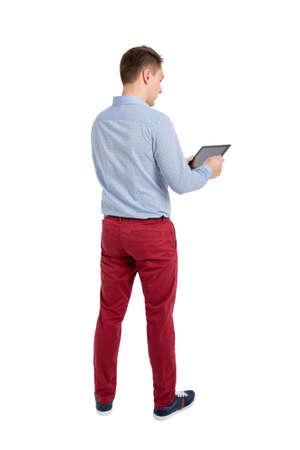 若い男性が立っていると、タブレットを使用してビューをバックアップします。人の裏面表示。白い背景に分離