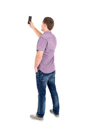 personas de pie: Vista posterior del pie hombres jóvenes y el uso de un teléfono móvil. Vista posterior recogida de las personas. Trasero vista de la persona. Aislado sobre fondo blanco