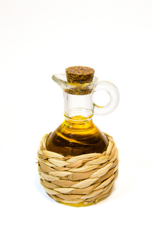 Straw braided bottle with oil isolated on white background