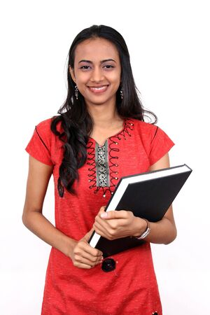 indian college student: Young teenage girl holding a book. Isolated on a white background.