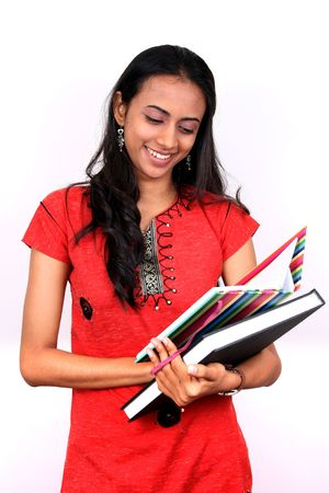 indian college student: Young teenage girl holding a book. Isolated on white background.