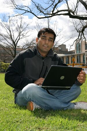 coursework: Indian student working on his laptop.