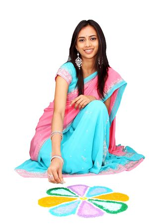 Young Indian girl drawing rangoli. Isolated on a white background.