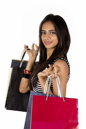 Young Indian girl shopping. Isolated on a white background.