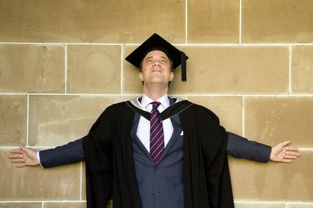 A portrait of a young European man in a graduation gown. photo