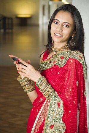 indianin: Młoda dziewczyna indyjskich w tradycyjny ubiór przy użyciu cellphone.