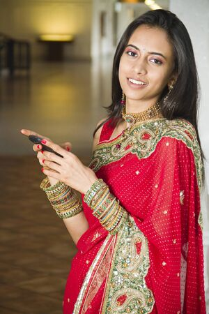 Young Indian girl in traditional clothing using a cellphone. Stock Photo