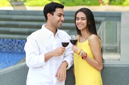 minority couple: Young romantic couple celebrating with wine.
