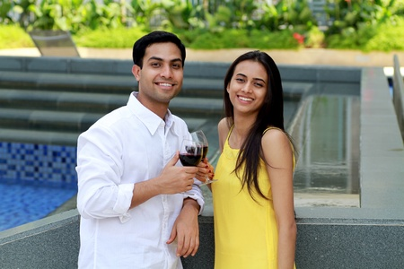 asian indian: Young romantic couple celebrating with wine.