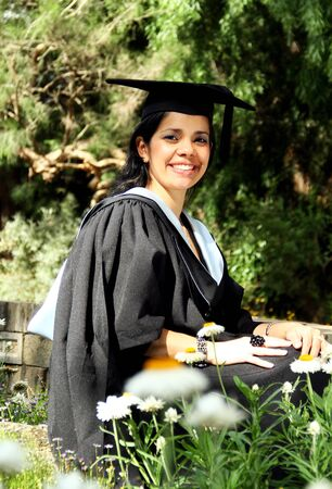 A portrait of a young girl girl in a graduation gown. photo