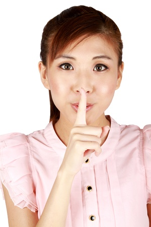 admonish: Young Asian business woman with finger on lips.