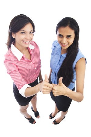 Happy cheerful Indian and Caucasian business women with their thumbs up.
