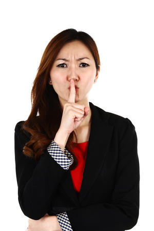 forefinger: Portrait of young Asian business woman keeping finger on her lips and asking to keep quiet, isolated on white background Stock Photo