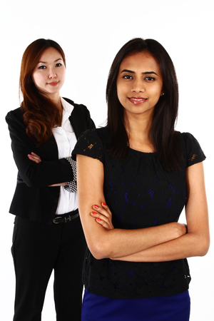 asian business women: Two happy young Asian business women standing together; on a white background Stock Photo