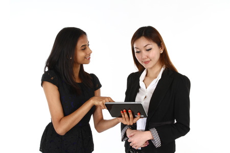 asian business women: Two happy young Asian business women presenting; on a white background  Stock Photo