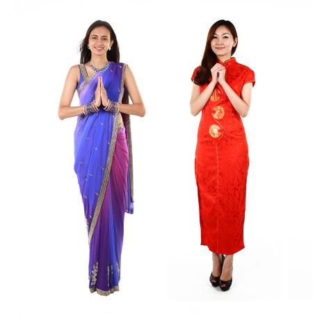 namaste: Mujer india y china joven en la ropa tradicional Foto de archivo