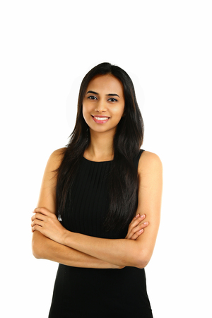 Close up portrait of a smiling Indian business woman with arms crossed isolated on white.