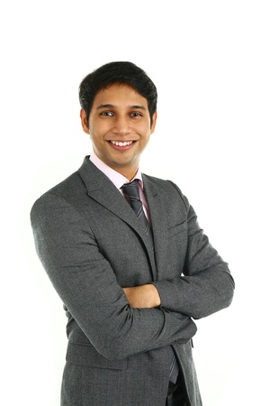 Close up portrait of a smiling Indian business man with arms crossed isolated on white. Stock Photo
