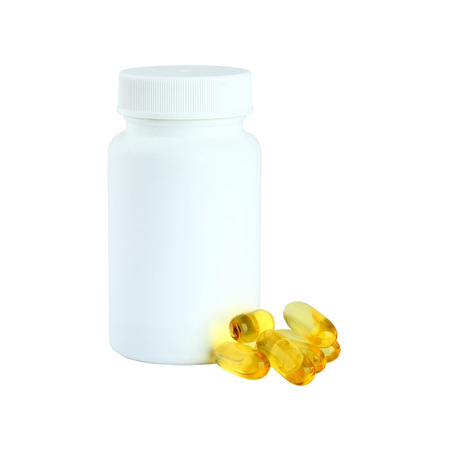 Yellow Cod Liver oil omega 3 gel capsules next to a bottle on white background