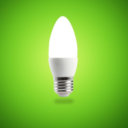 Glowing LED energy saving bulb on green background Stock Photo