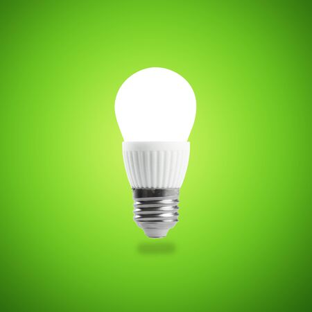 Glowing LED energy saving bulb on green background. Stock Photo