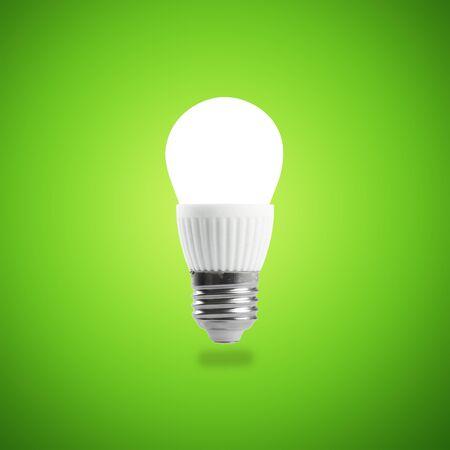 Glowing LED energy saving bulb on green background. Stock Photo