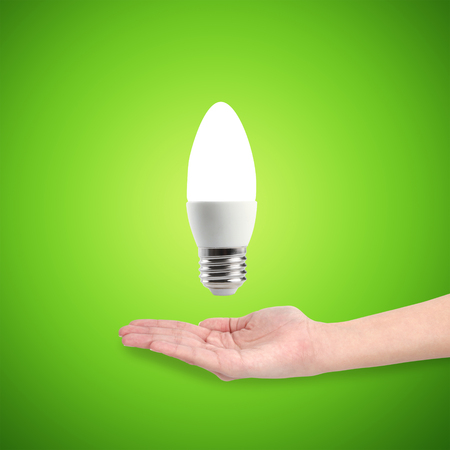 Glowing LED energy saving bulb in a hand over a green background